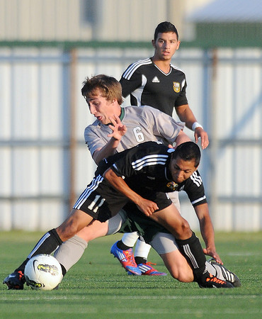 Norman North midfielder Michael Henke (6) and Chris Perez (11) scrmble for the ball Tuesday, May 8, 2012, during a Class 6A boys soccer semifinal game. Photo by Jerry Laizure