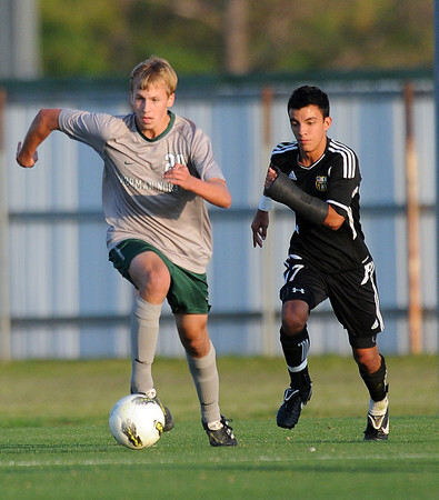 Norman North midfielder Jonanthan Newton (20) advances the ball past Broken Arrow defender Jeremy Rector (17)  Tuesday, May 8, 2012, during a Class 6A boys soccer semifinal game. Photo by Jerry Laizure