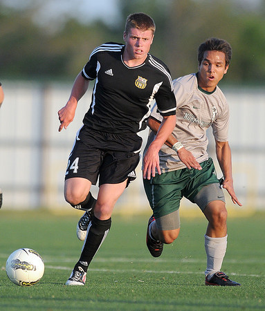 Broken Arrow's Tyler Hill (24)  advances the ball while Norman North's Brandon Little Axe (3) pursues him  Tuesday, May 8, 2012, during a Class 6A boys soccer semifinal game. Photo by Jerry Laizure
