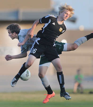 Broken Arrow's Landen Merrill (16) and Norman North's Ian Bergman (24) battle for the ball Tuesday, May 8, 2012, in a Class 6A semifinal game in Norman. Photo by Jerry Laizure