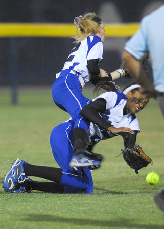 Moore High School's Caiti Hall (2) and Brianna McArthur (12) collide as they both try to catch a fly ball during the Lions' game against Edmond North during the 6A state softball championships at the ASA Hall of Fame Stadium in Oklahoma City.<br /> Kyle Phillips/The Transcript