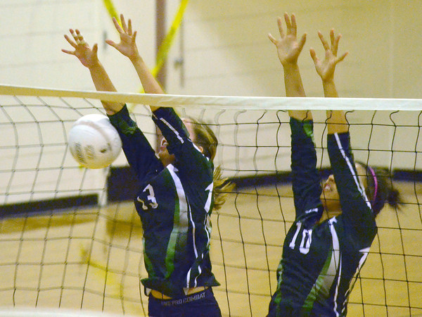 Norman North's McKayla Benner (10) and Haley Reed (13) block a shot by Norman High Tuesday during the Clash volleyball game at Norman High School.<br /> Kyle Phillips/The Transcript