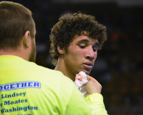 Moore High Assistant Wrestling Coach  wipes blood from McKale Washington's face during his match against Jenks' Austin Eades Friday during the first round of the Oklahoma High School Wrestling Championships.<br /> Kyle Phillips/The Transcript