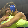 Moore High School's McKale Washington hugs his coach after he wins his match in the first round of the Oklahoma High School Wrestling Championships at the State Fair Arena in Oklahoma City.<br /> Kyle Phillips/The Transcript