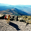 "10/19/94: Mt Washington #16: Lindsey ""Bear"" Comparato sporting her own backpack after climbing Mt.Washington. Mt.Monroe and Lakes of the clouds in the background."