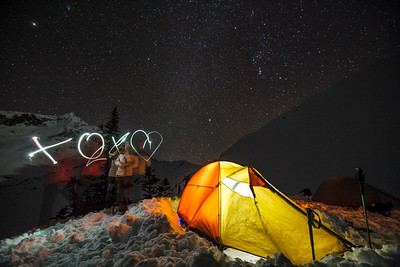A young couple spell out XOX followed by a heart with their headlamps while camping in British Columbia, Canada.