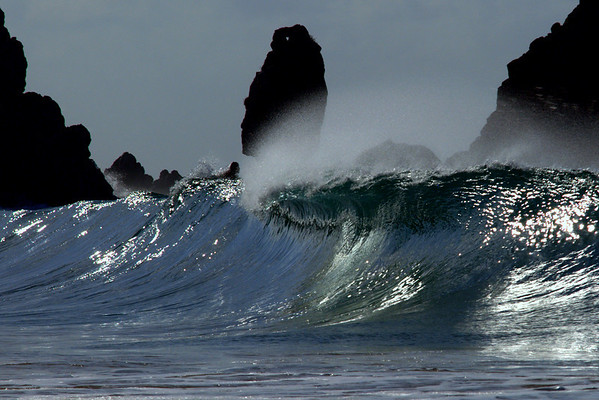 Head to head with the surf: Notice the surfer on the top of the wave facing the headlike rock formation in the background