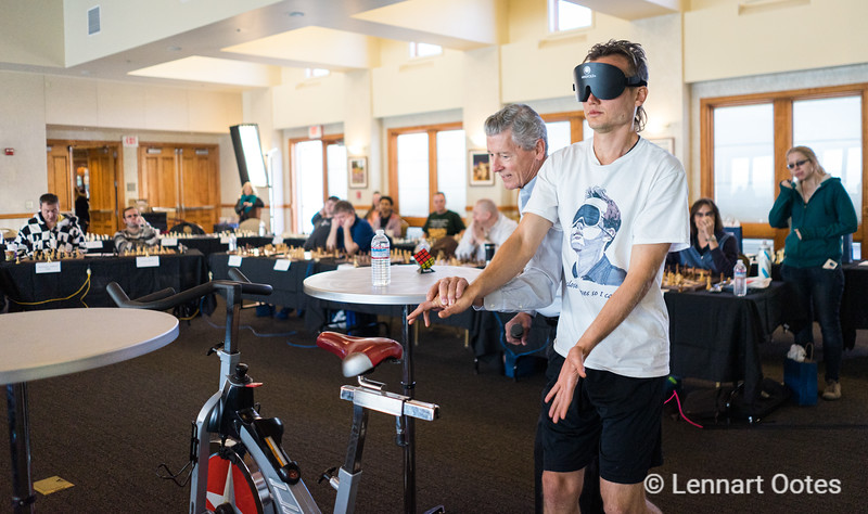 Timur Gareyev is guided back to his stationary bike after a brief toilet break. Gareyev broke the World Record for Blindfold Chess after he played 48 players in a simul that lasted 19 hours.