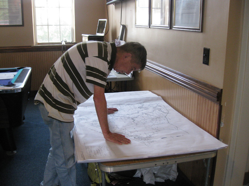 Bill Culler closely examines a 1941 base area map that shows the location of all former landowners and the listing of their names.