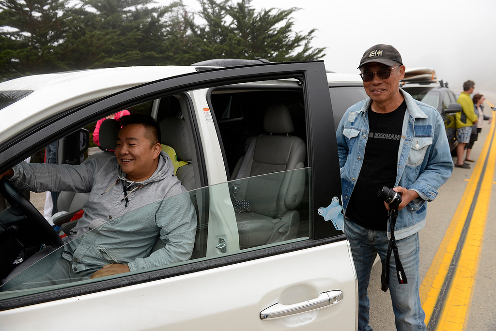 . Tiaulun Jiang and Zhenchao Ma from visiting from China wait in Gorda on Wednesday, July 18, 2018 for Highway 1 to reopen at the Mud Creek slide south of Big Sur was after more than a year of being closed.  (Vern Fisher - Monterey Herald)