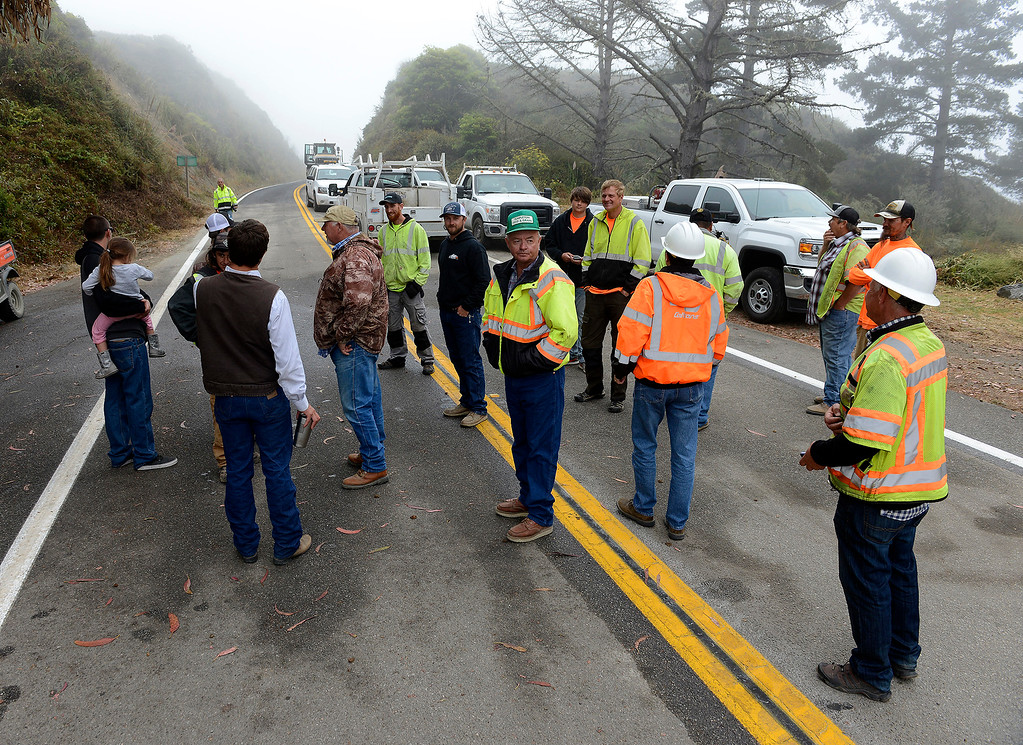 . Caltrans officials with members of the construction crew wait at the Gorda roadblock for the new section of Highway 1 at the Mud Creek slide south of Big Sur to reopen on Wednesday, July 18, 2018.  (Vern Fisher - Monterey Herald)