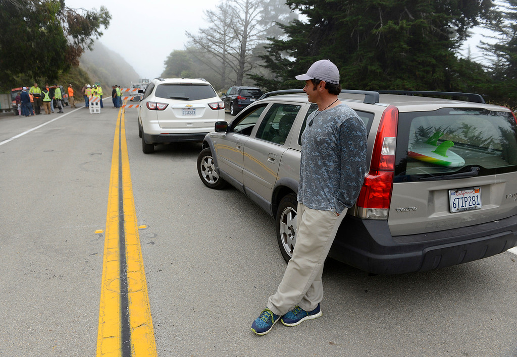 . Matt Romano from Pacific Grove waits at the road block in Gorda for Highway 1 to reopend at the Mud Creek slide south of Big Sur on Wednesday, July 18, 2018.  Romano was the first motorist to drive the new section of roadway.  (Vern Fisher - Monterey Herald)