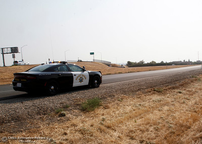 A CHP squad car waits on the Highway 99 southbound onramp at Skyway for the word from PG&E to shut down the highway. The utility needed to stretch a power line across Highway 99 near Neighborhood Church on Tuesday, Aug. 21, 2018, after a power pole was damaged during a high-speed chase Monday. The California Highway Patrol closed the highway for less than 10 minutes from Skyway to Southgate Avenue in both directions for the work. (Dan Reidel -- Enterprise-Record)
