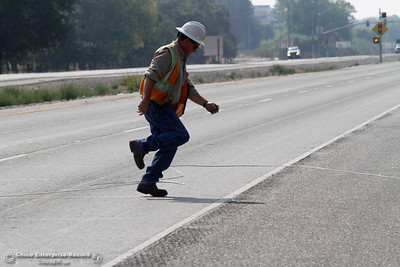 PG&E stretches a power line across Highway 99 near Neighborhood Church on Tuesday, Aug. 21, 2018, after a power pole was damaged during a high-speed chase Monday. The California Highway Patrol closed the highway for less than 10 minutes from Skyway to Southgate Avenue in both directions for the work. (Dan Reidel -- Enterprise-Record)