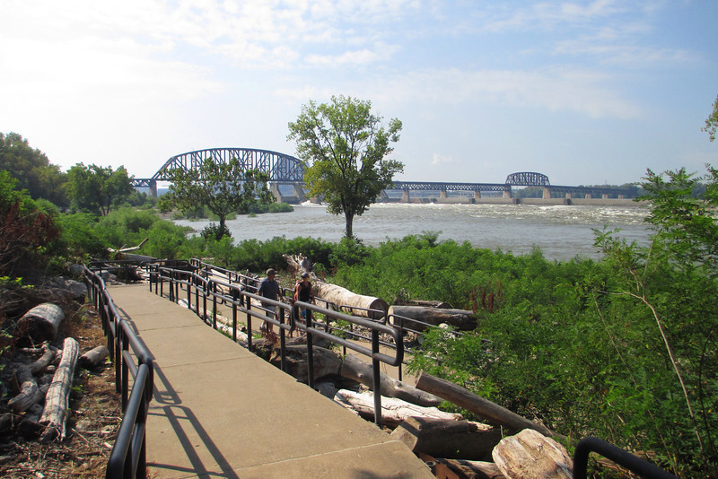 From the visitor center parking lot a winding concrete path leads down to the rivers edge and the fossil beds.  The steel bridge in the background carries US-31 over the Ohio...