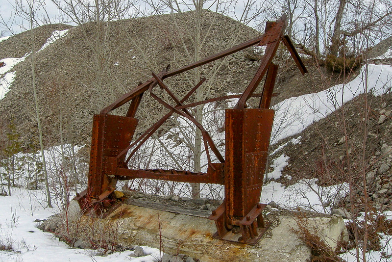 Scattered on and around the tailing piles are bent, rusted remnants of the industry that once existed here...