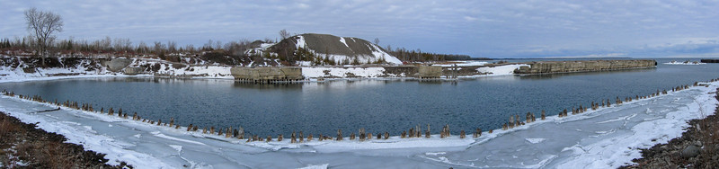 A panoramic shot of the old Rockport deep-water harbor with the pier extending towards the lake to the right...