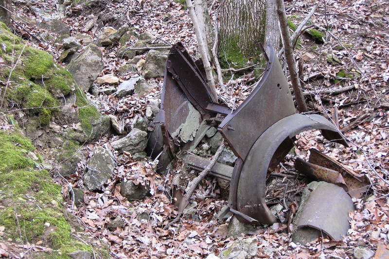 At the bottom of the first hill some old, rusted car parts lie along the trail...
