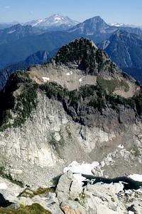View east from the summit of Vesper Peak. Sperry Peak near, behind it Sloan Peak and in distance the Glacier Peak.