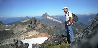Summit od Cadet Peak. Sloan Peak in the distance. Selftimer photo. Solo hiker. Glacier Peak Wilderness.