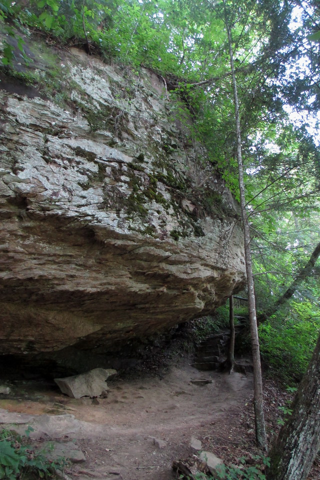 A precursor of of things to come, the trail winds beneath a massive rock overhang...
