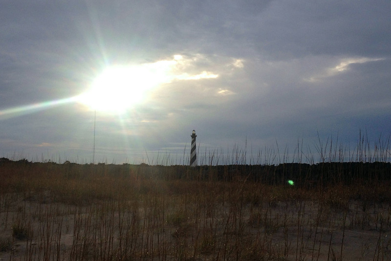A brief break in the clouds gives the sun a chance to flash through above the Hatteras light...