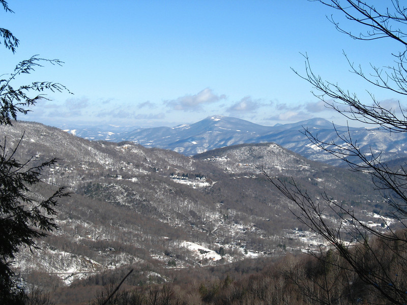 A slightly closer look at Foscoe View. Foscoe and the thin stripe of Hwy. 105 line the valley below. The mountains in the distance are part of the Amphibolite Range. I believe Rich Mountain is the peak in the center and Elk Knob is to the right above the tree branch.