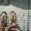 Whose beautiful hiking boots are these? She is not afraid of the raging river below.