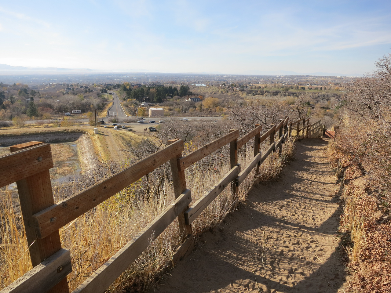 Sandy switchbacks lined by fence and bushy oaks climb fast to views of Layton.