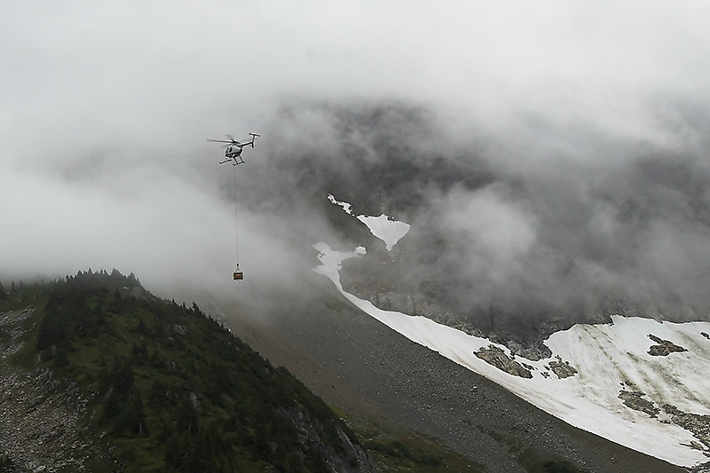 Helicopter supplying trail workers with gravel taken from base of glacier
