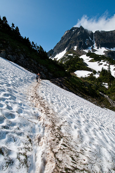 Crossing one of the remaining snow fields before Cascade Pass.