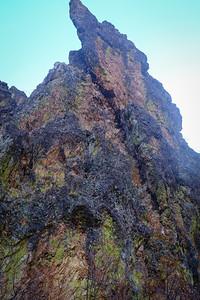 Textured rocks reach steeply up.