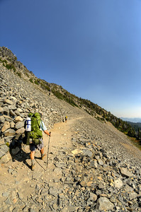 A overnight backpacker passes by the stone wall on Sourdough Ridge Trail. This is one of the frames from the 360 panorama.