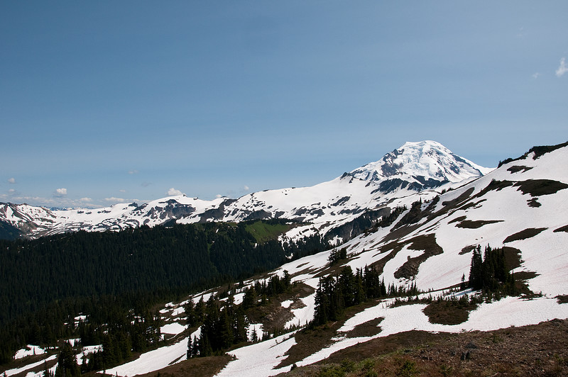 The trail follows to the right and over the snowfields.