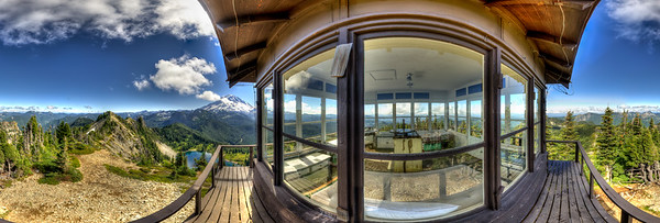 Tolmie Peak Fire Lookout, Mt. Rainier National Park, Washington State. Mt. Rainier is framed under the eve of the fire lookout tower on the summit of Tolmie Peak on the Northwest side of Mt. Rainier National Park, in Washington State. With 1,200 feet of elevation gain over 7.2 miles round trip it's a moderate hike, with fantastic views of the north face of Mt. Rainier. The trail starts at Mowich Lake and passes Eunice Lake (visible below) before ascending to Tolmie Peak. There are huckleberries and wildflower meadows on the south side on the way up.