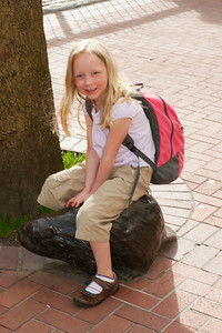 Hannah riding a beaver statue near Pioneer Courthouse in Portland