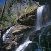 There is a huge, recessed spray cliff to the right behind the waterfall.  To the left, down stream and out of sight, is a moss-covered rock wall.  I estimate the height of the waterfall to be thirty-one feet; + or -