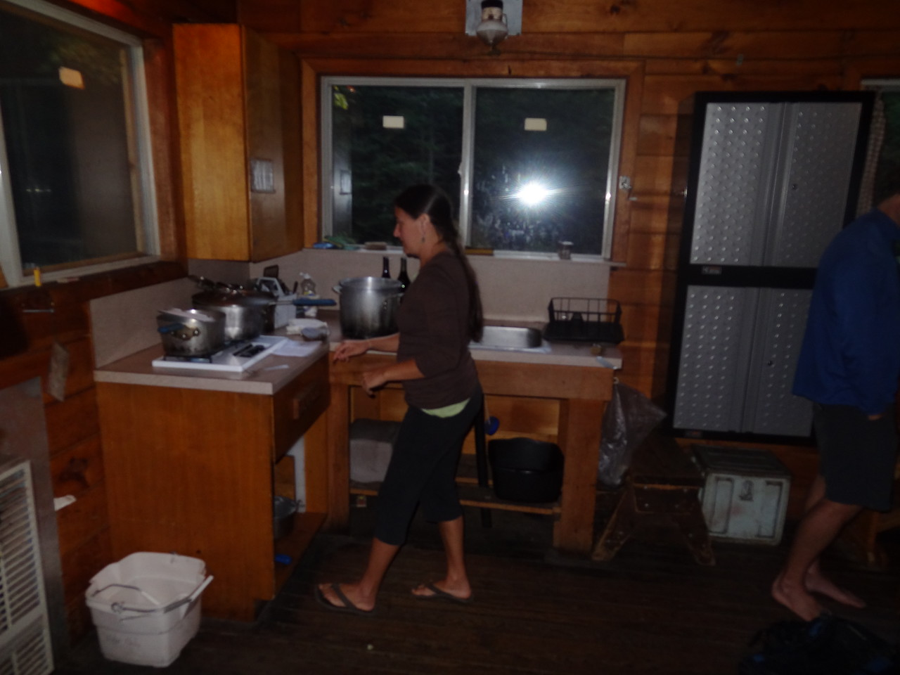 Grace cabin. It was the size of a big 1 car garage, but had all the necessities. Robin is cooking our cous cous on the propane stove. Propane heater is to the left. Propane light above her head, and sink behind her. The sink requires potable water but no need for digging and burying anything.