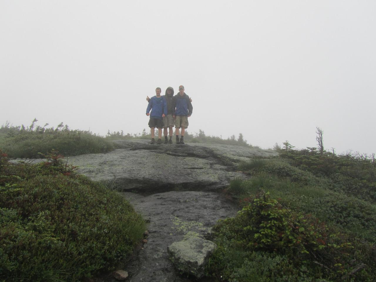 At the summit of Colden in the pouring rain. Smiles gone from the boys faces. Bob is still going strong! Two thumbs up. Men rule, boys drool.