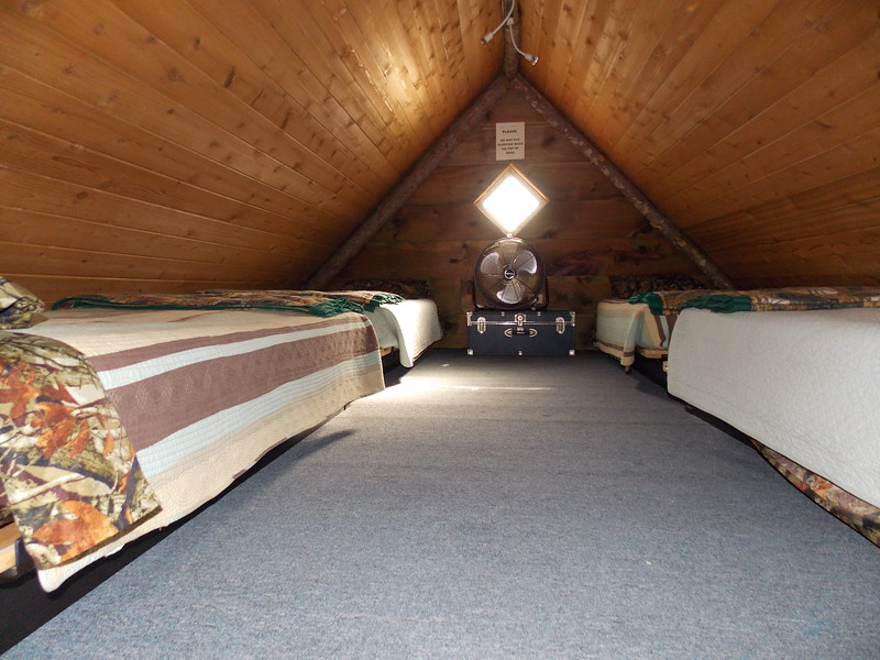 Four beds in the loft, a queen bed below in an alcove, and an unheated bunkroom below.