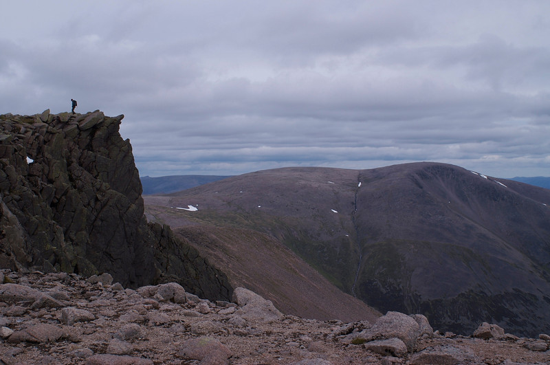 A walker near Braeriach summit with Ben Mcdui across the Lairig