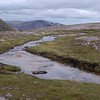 One of the feeder streams of Allt a Gharbh-Choire, and thus of the river Dee, flowing across the summit plateau of Braeriach from the Wells of Dee.  Just beyond sight, the stream dives beneath a lingering snowfield and emerges in a long waterfall to fall most of the height of the Choire