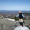 Brother Pat enjoys the views from the ledges of Firescrew.  Snow-capped peaks of Franconia Ridge and Mt Washington in the distance.