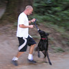 Another hiker running by, playing tug with his Labrador Retriever.