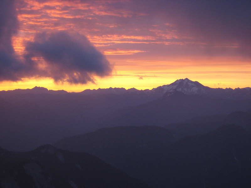 A stiff wind chases clouds and constantly closes and opens new views to the fiery sunrise.