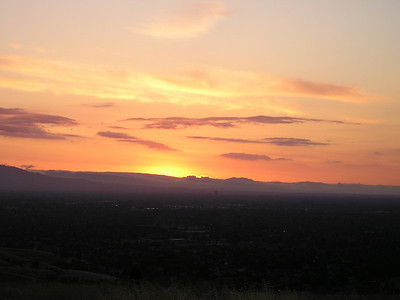 As the sun sinks slowly into the west--and the edges of the clouds gleam a fiery orange--