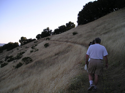 The trail wraps around and climbs up the steep hillside.