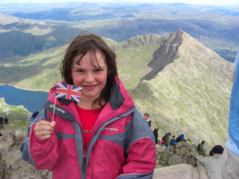 Celia claims Snowdon for the UK.  Glaslyn and the ridge of Y Lliddaw are behind her, with the Llanberis Pass beyond.  I think the triangular peak in the far distance to right of centre is Moel Siabod - the next picture of Snowdon was taken from there the following day