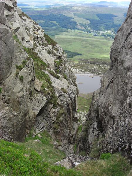 Dolwyddelan seen through a gully on Moel Siabod ridge, with Llyn y Foel below