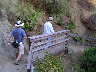 William and Denny cross a bridge.